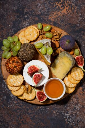 Cheese, crackers and fresh fruits, delicious wine snacks on dark Stock fotó