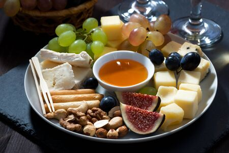 Plate with deli snacks and glasses of wine, closeup, horizontal Stock fotó - 136028880