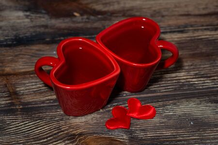 two red cups of tea in the shape of hearts on a wooden background, top view Banco de Imagens