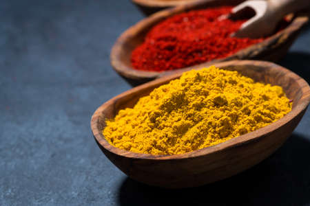 ground spicy paprika, turmeric and red pepper in a wooden bowl, closeup, horizontal Standard-Bild