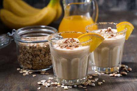 healthy milkshake with oatmeal, banana and orange on dark table, closeup horizontal Standard-Bild