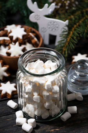 jar with sweet marshmallows and Christmas decorations on wooden table, vertical top view Standard-Bild