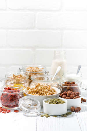 ingredients for healthy breakfast on white table, vertical
