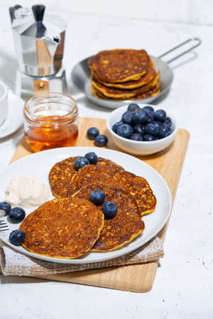 homemade pancakes with fresh blueberries and yogurt on white background, vertical