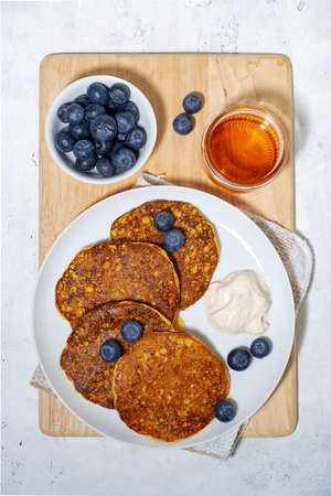 homemade pancakes with blueberries and yogurt on white background, top view