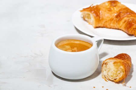 cup of espresso and fresh croissants on white background, closeup horizontal Standard-Bild