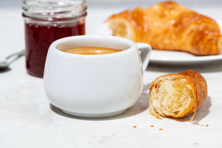 cup of espresso and fresh croissants, berry jam on white background, closeup horizontal Standard-Bild