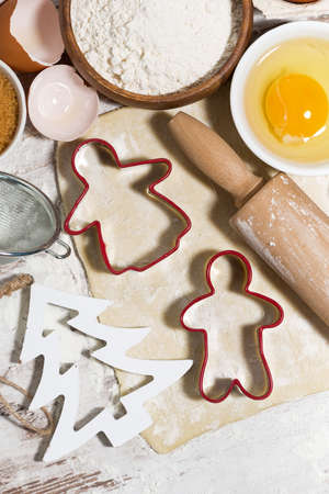 Ingredients for baking Christmas cookies. Dough, various cookie cutters and rolling pin, vertical top view Standard-Bild