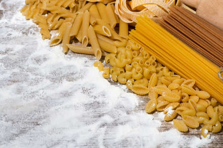 different dry pasta on a wooden board with flour, top view, horizontal
