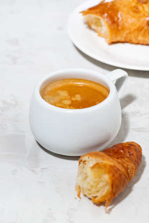 cup of espresso and fresh croissants, vertical top view Standard-Bild