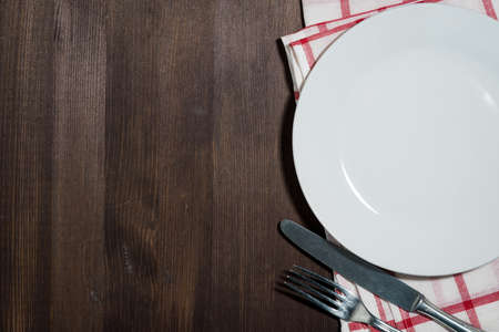 empty plate and cutlery, wooden background for recipes, top view