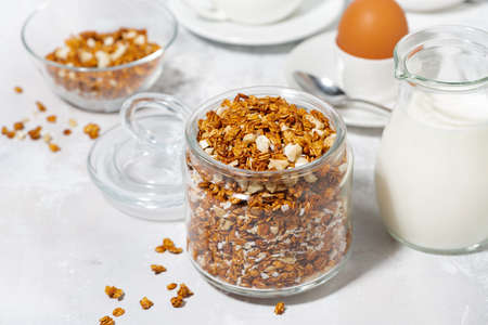 jar of granola with coconut and nuts on white background, horizontal