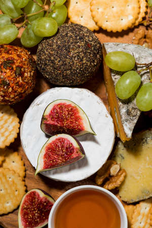 delicious snacks, cheese, crackers and fresh fruits, top view