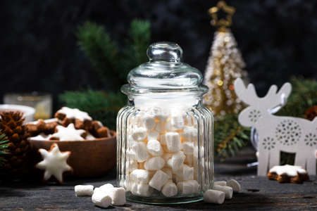 jar with sweet marshmallows and Christmas decorations on wooden table, horizontal