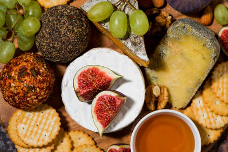 delicious snacks, cheese, crackers and fresh fruits, top view horizontal