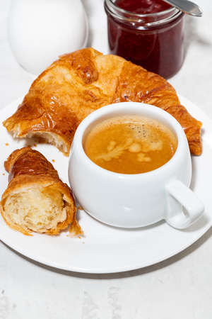 cup of espresso and fresh croissants on white background, top view vertical Standard-Bild