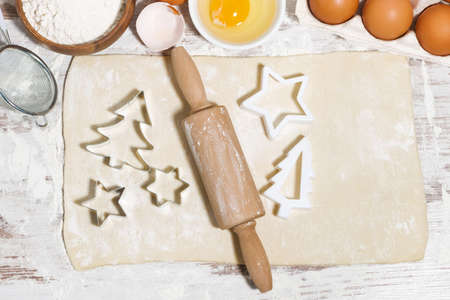 Ingredients for baking Christmas cookies. Dough, cookie cutters and rolling pin, top view