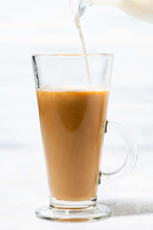 milk is poured into a glass cup with coffee, closeup vertical