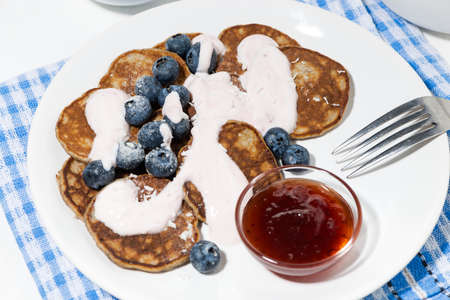 homemade pancakes with blueberries and jam, top view closeup