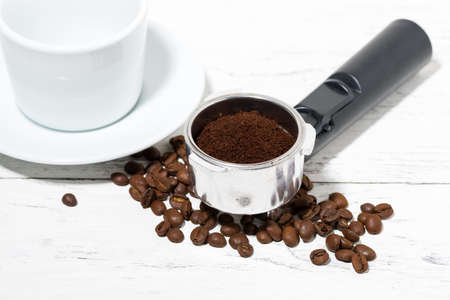 holder with ground coffee and empty cup on white background, horizontal