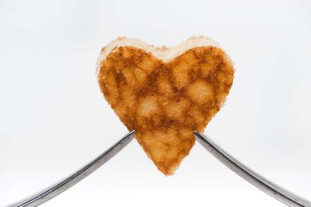 heart shaped pancake on two forks, closeup horizontal