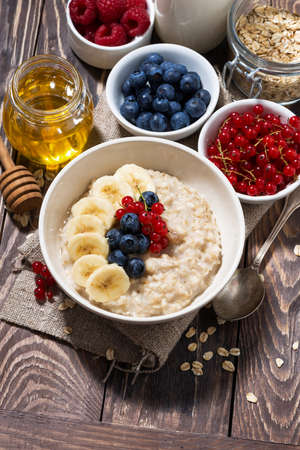 homemade oatmeal with berries on wooden background, top view Standard-Bild