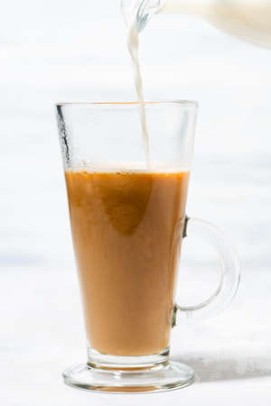 milk is poured into a glass cup with coffee, vertical closeup Standard-Bild