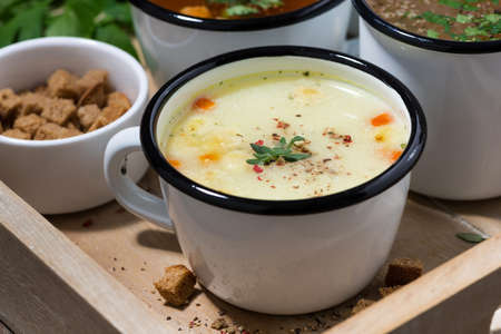 hot soups in mugs on wooden tray, closeup, horizontal