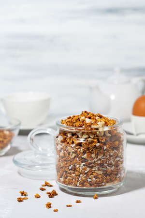 jar of homemade granola with coconut and nuts on white background, vertical closeup Standard-Bild