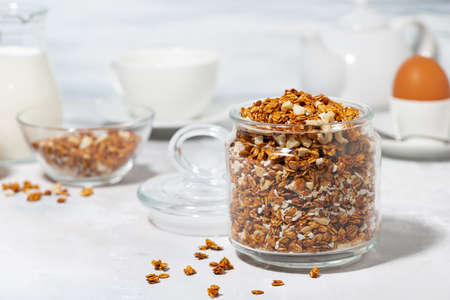 jar of homemade granola with coconut and nuts on white background, horizontal