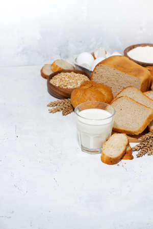 glass of milk, assortment of fresh bread and ingredients on white table, top view Standard-Bild