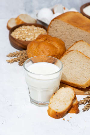 glass of milk, assortment of fresh bread and ingredients on white background, vertical closeup Standard-Bild