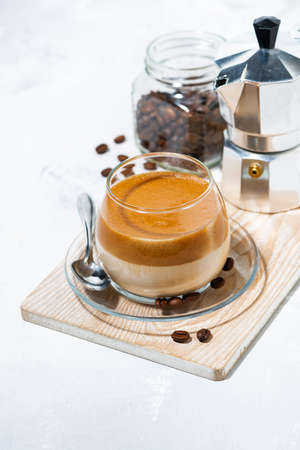 milky coffee with cream foam in glass, top view vertical