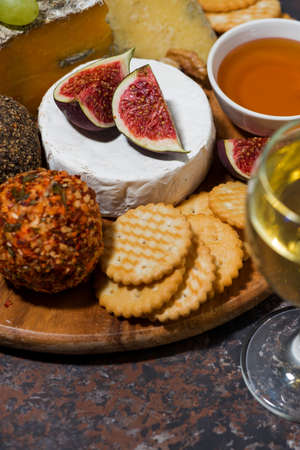 gourmet cheeses with a glass of white wine, closeup vertical