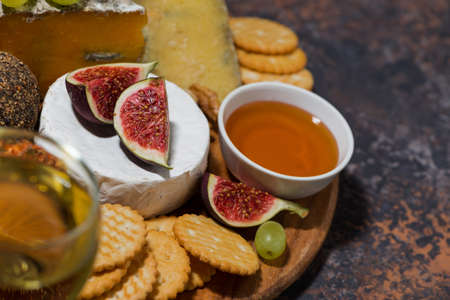 gourmet cheeses with a glass of white wine, top view Standard-Bild