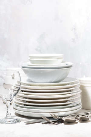Tableware, cutlery and glasses on a white table