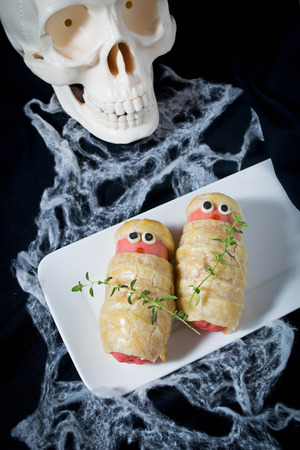 treat like a dog: Halloween sausage in the dough decorated to look like mummies  Stock Photo