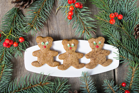 Christmas gingerbread cookies on wooden background with fir-tree photo