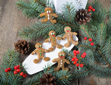 Christmas gingerbread man on wooden background with fir-tree photo