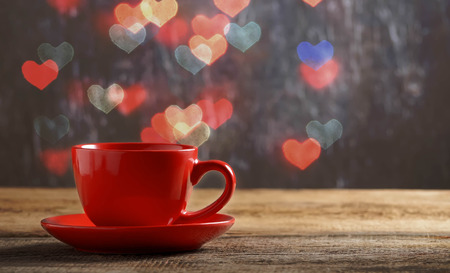 pretty s shiny: Red cup of tea in defocused heart bokeh background. Valentine 's Day