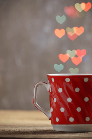 Red cup of tea in defocused heart bokeh background. Valentine 's Day