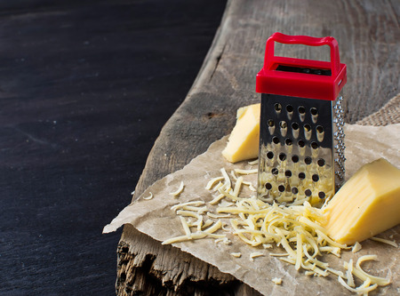 metal grater: Grated cheese and metal grater on paper Stock Photo