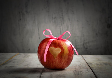 Ripe fresh apple with heart for Valentine day. Toned photo
