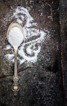 Sea salt in spoon on old grange metal background photo