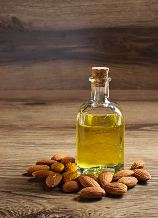 Bottle with almond oil on wooden background