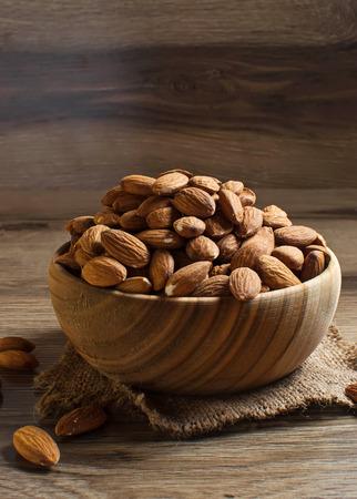 Almonds in brown bowl on wooden background 版權商用圖片