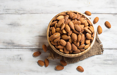 Almonds in brown bowl on wooden background 스톡 콘텐츠