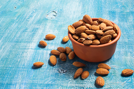 Almonds in brown bowl on wooden background 免版税图像