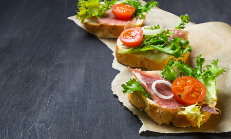 spanish onion: Traditional Italian antipasti crostini with ham, salad and tomato. Selective focus. Space for text Stock Photo