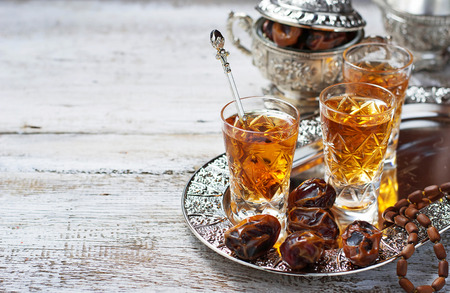 Traditional arabic tea and dry dates. Selective focus. Space for text
